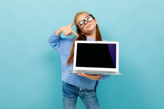 Aantrekkelijk europees meisje toont een laptop scherm met mockup in haar handen op lichtblauw