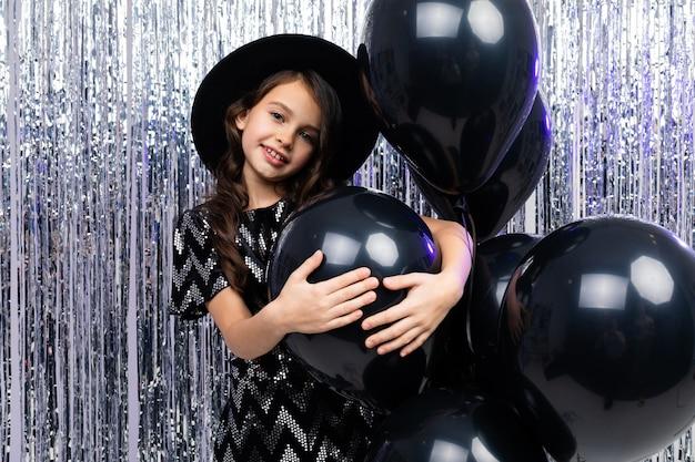 Aantrekkelijk europees zonnig tienermeisje op vakantie op de achtergrond van zwarte heliumballons en klatergoud