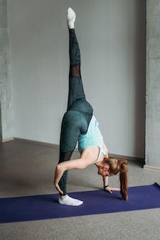 Aantrekkelijk fit jonge vrouw sport slijtage fitness meisje doet het uitrekken bij loft studio training klasse
