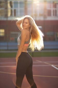 Aantrekkelijk fitnessmodel met perfect lichaam en lang weelderig haar poseren op een tennisbaan in zonnestralen