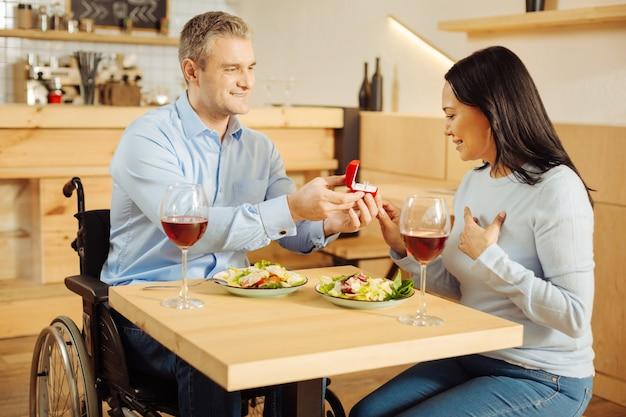 Aantrekkelijk geïnspireerde gehandicapte man die lacht en zijn mooie geliefde donkerharige vrouw voorstelt en een ring vasthoudt tijdens een romantisch diner