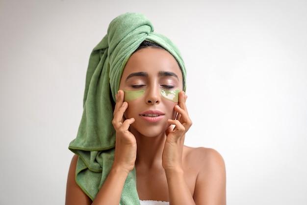 Aantrekkelijk gelooid meisje legt na het douchen patches onder haar ogen.