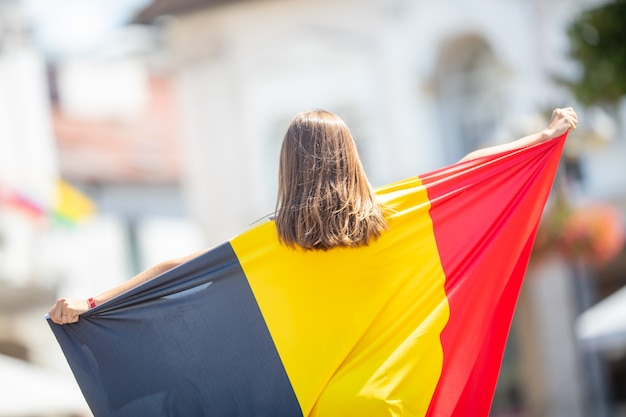 Aantrekkelijk gelukkig jong meisje met de belgische vlag