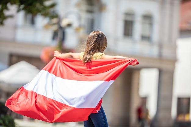 Aantrekkelijk gelukkig jong meisje met de vlag van oostenrijk.