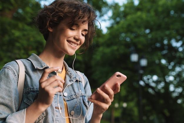 Aantrekkelijk gelukkig jong meisje met een casual outfit die tijd buitenshuis doorbrengt in het park, naar muziek luistert met oortelefoons, mobiele telefoon vasthoudt