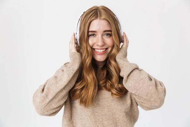 Aantrekkelijk gelukkig jong meisje met een trui die over een witte muur staat en een koptelefoon draagt