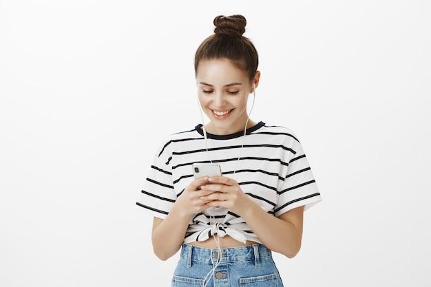 Aantrekkelijk gelukkig meisje in koptelefoon, muziek luisteren en glimlachen op smartphonescherm, messaging, toepassing gebruiken of video kijken