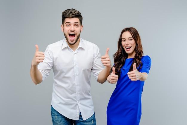 Aantrekkelijk gelukkig paar die duimen tonen die omhoog over grijze achtergrond worden geïsoleerd