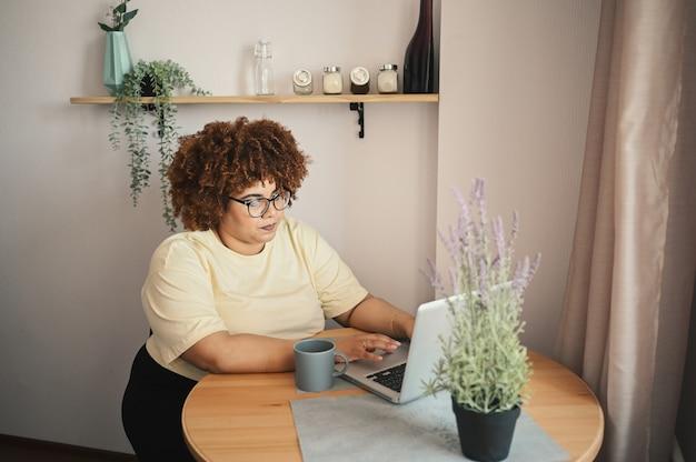 Aantrekkelijk gelukkig stijlvol plus size afrikaanse zwarte studente afro haar in een bril die online studeert