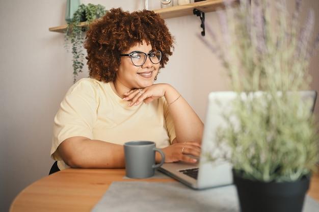 Aantrekkelijk gelukkig stijlvol plus size afrikaanse zwarte studente afro haar in een bril die online studeert Premium Foto