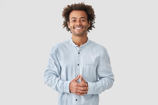 Aantrekkelijk gemengd ras man met een positieve glimlach, witte tanden vertoont, handen op de buik houdt, in een hoge geest is, een wit overhemd draagt, verheugt zich over positieve momenten in het leven. mensen en emoties concept