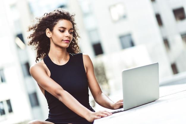 Aantrekkelijk gemengd rasmeisje met mooi afrohaar dat glimlacht terwijl ze naar haar laptopscherm kijkt