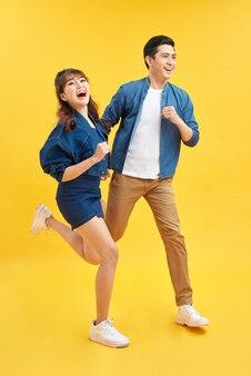 Aantrekkelijk glimlachend jong aziatisch paar dat gelukkig en verbaasd is geïsoleerd op gele studioachtergrond