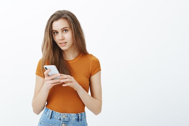 Aantrekkelijk glimlachend meisje met behulp van mobiele telefoon, sms-bericht, applicatie downloaden of video kijken
