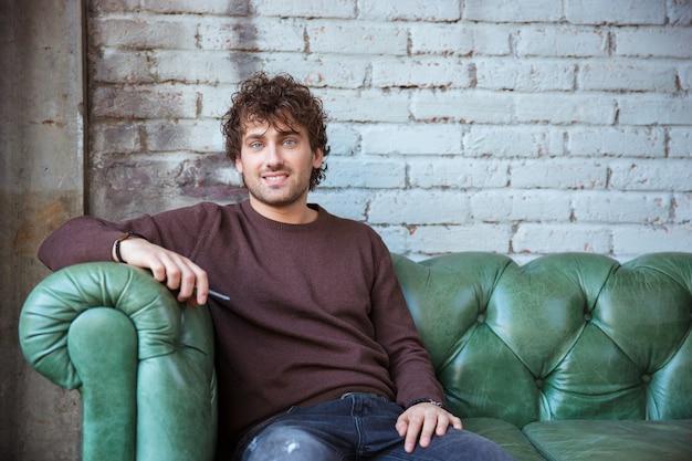 Aantrekkelijk glimlachend vrolijk tevreden tevreden positief krullend zelfverzekerd mannetje in bruin sweetshirt en jeans zittend op een groene leren bank