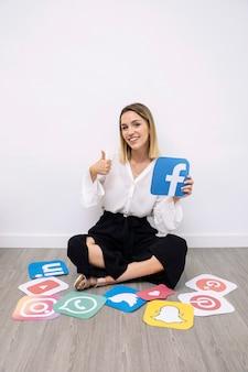 Aantrekkelijk glimlachend vrouw die facebook pictogram houden dat thumbup teken toont