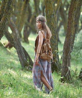Aantrekkelijk hippiemeisje die door het bos lopen. het concept van eenheid met de natuur