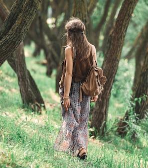 Aantrekkelijk hippiemeisje die tussen de bomen in het bos lopen. het concept van eenheid met de natuur