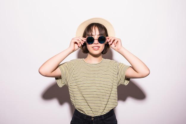 Aantrekkelijk hipster mode tienermeisje in hoed, zonnebril in witte muur