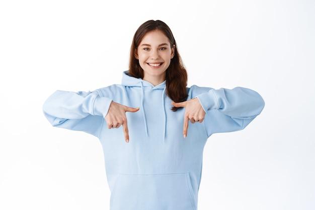 Aantrekkelijk hipstermeisje met gelukkige glimlach die promotionele tekstadvertenties toont, vingers naar beneden wijst naar het logo, uitnodigende check-out promo, staande over een witte muur