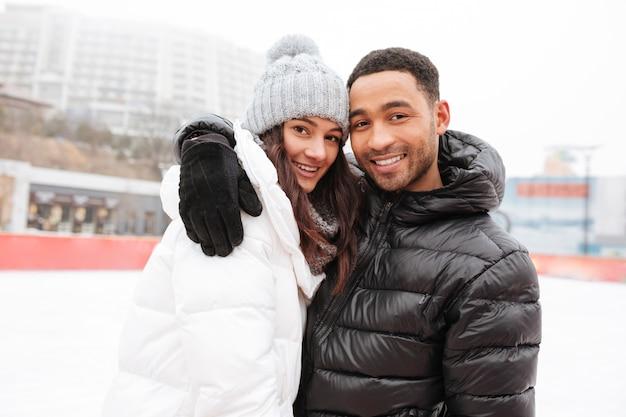 Aantrekkelijk houdend van paar die bij ijsbaan in openlucht schaatsen.