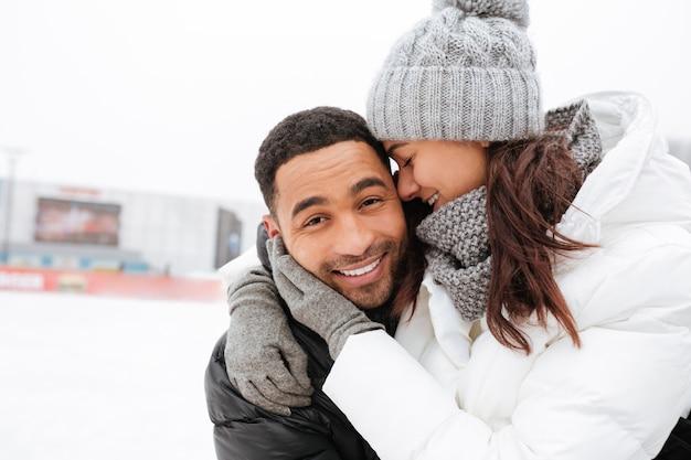 Aantrekkelijk houdend van paar die en bij ijsbaan koesteren schaatsen