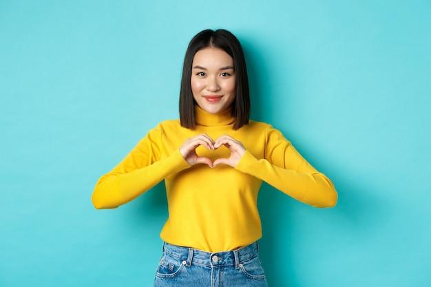 Aantrekkelijk japans meisje in gele trui, hartgebaar tonen en zeggen dat ik van je hou, oprecht naar de camera kijkend, staande over blauwe achtergrond
