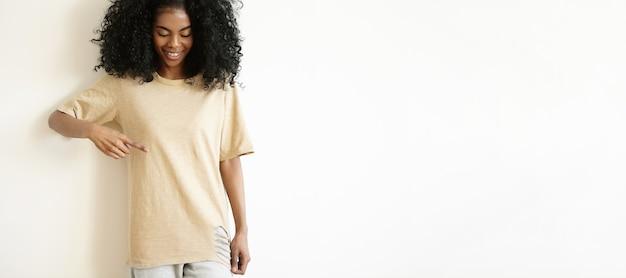 Aantrekkelijk jong afrikaans vrouwelijk model dat casual t-shirt draagt, en haar lege t-shirt glimlacht toont
