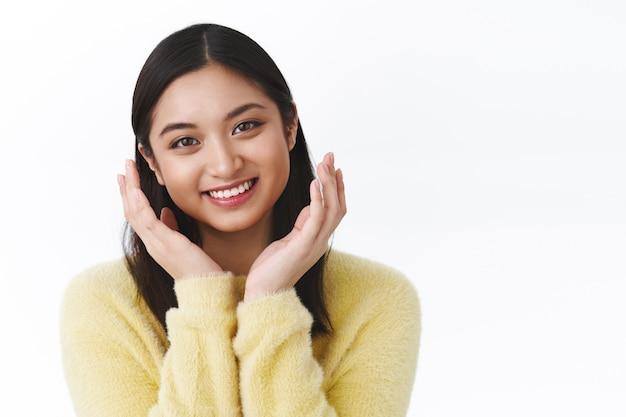 Aantrekkelijk jong aziatisch meisje promoot koreaanse make-up, breng huidverzorgingsroutineproduct aan, hand in hand in de buurt van wangen in mooie schattige pose, glimlachende kawaii, witte muur