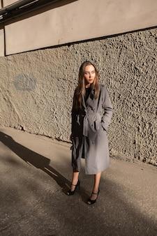 Aantrekkelijk jong aziatisch model in grijze trenchcoat die buiten in de buurt van de muur staat