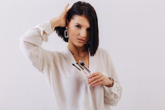 Aantrekkelijk jong bedrijfsmeisje met make-upborstels die op duidelijke achtergrond stellen. concept van make-up en cosmetica.