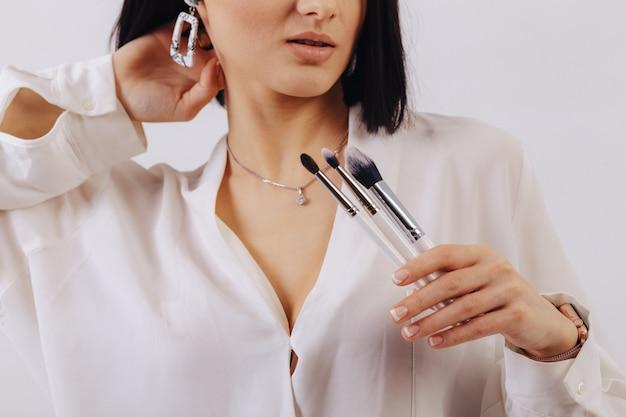 Aantrekkelijk jong bedrijfsmeisje met make-upborstels die op duidelijke muur stellen. concept van make-up en cosmetica.