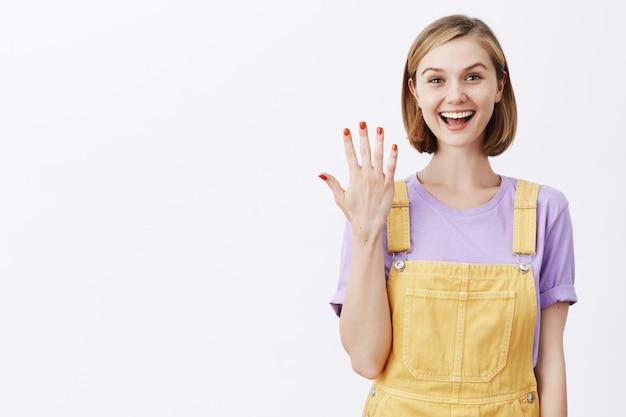 Aantrekkelijk jong blond meisje dat nummer vijf of nagellak toont