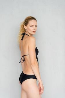 Aantrekkelijk jong blonde model in het zwarte swimsut stellen in studio