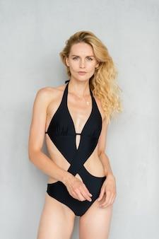Aantrekkelijk jong blonde model in het zwarte swimsut stellen