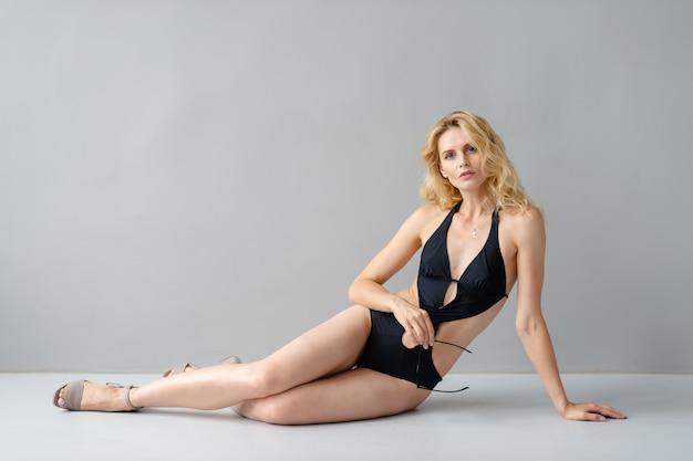 Aantrekkelijk jong blonde model in het zwarte zwempak stellen