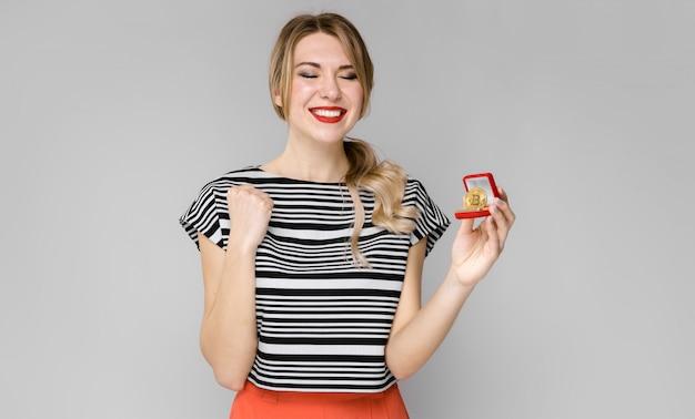 Aantrekkelijk jong blondemeisje in gestreepte blouse die tonend bitcoin glimlachen als cryptocurrency-concept die zich op grijze achtergrond bevinden