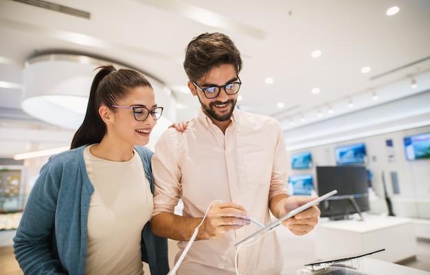 Aantrekkelijk jong hipsterpaar die een tablet met een elektrische pen controleren terwijl het winkelen in de elektronische winkel.