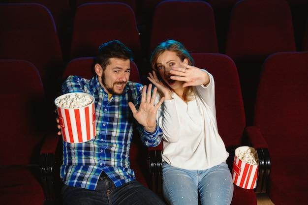 Aantrekkelijk jong kaukasisch paar dat een film bekijkt in een bioscoop, een huis of een bioscoop. zie er expressief, verbaasd en emotioneel uit. alleen zitten en plezier maken. relatie, liefde, familie, weekendtijd.