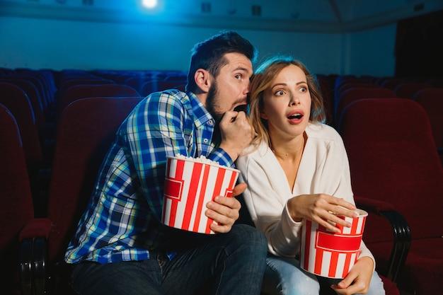 Aantrekkelijk jong kaukasisch paar dat een film bekijkt in een bioscoop, een huis of een bioscoop.