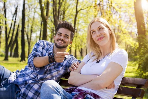 Aantrekkelijk jong koppel flirten en plezier hebben op een bankje in het park