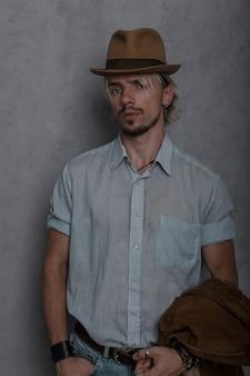 Aantrekkelijk jong mannelijk model met een baard in elegante ouderwetse kleding in een vintage hoed staat in de studio bij een grijze muur.