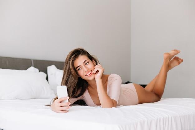 Aantrekkelijk jong meisje dat in de ochtend selfie op telefoon op bed in appartement neemt.