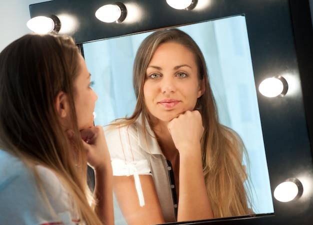 Aantrekkelijk jong meisje dat in de spiegel staart