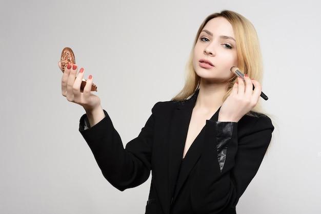 Aantrekkelijk jong meisje doet make-up artist zelf met een spiegel