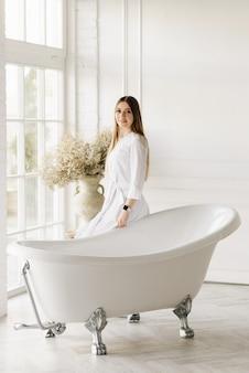 Aantrekkelijk jong meisje in een lichte jurk in de buurt van een luxe bad