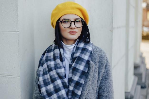 Aantrekkelijk jong meisje in glazen in jas en gele baret op een eenvoudige lichte ondergrond
