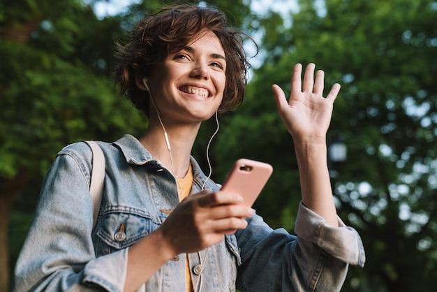 Aantrekkelijk jong meisje met een casual outfit die tijd buitenshuis doorbrengt in het park, naar muziek luistert met oortelefoons, mobiele telefoon vasthoudt, hand zwaait
