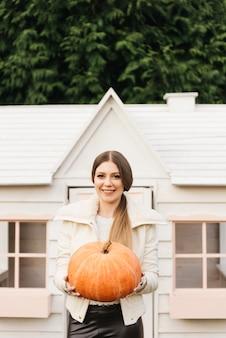 Aantrekkelijk jong meisje met een pompoen in haar handen buiten haar huis