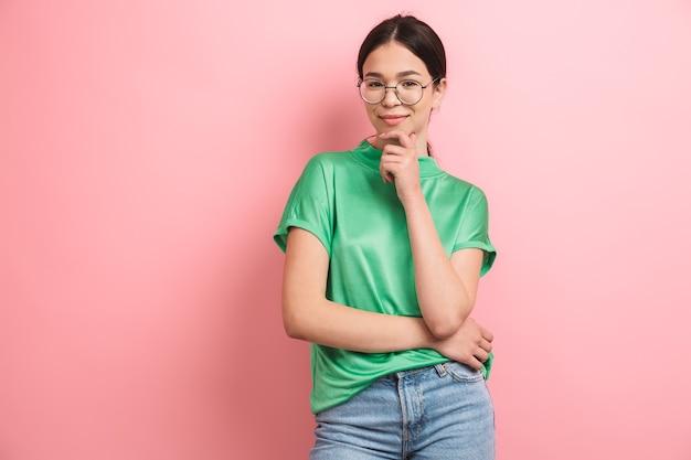 Aantrekkelijk jong meisje met een ronde bril die haar kin aanraakt en aan de voorkant glimlacht, geïsoleerd over roze muur